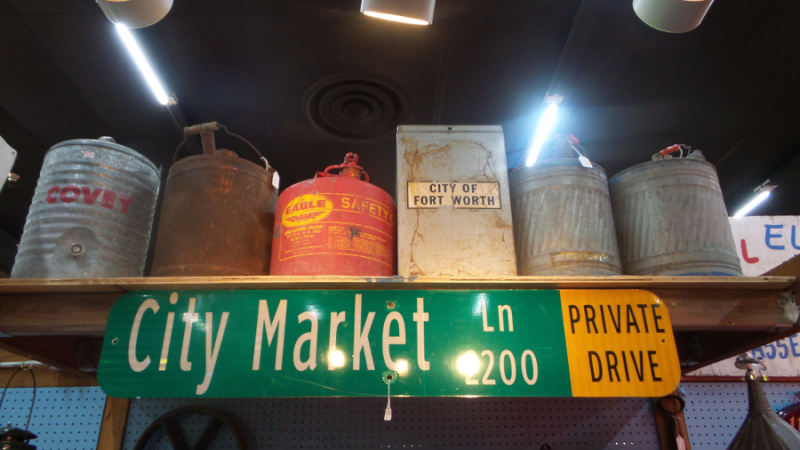"An image of Dealer #0924s booth, showcasing a green street sign that reads ""City Market Ln 2200 Private Drive"". There is a shelf above it that has six different vintage buckets and canisters."