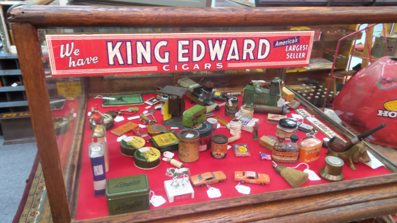A picture of a display in Dealer #0924's booth. The bottom of the display isred and there is an assortment of antiques on display. There is also a vintage advertisement for King Edward Cigars that is hanging in the display case.