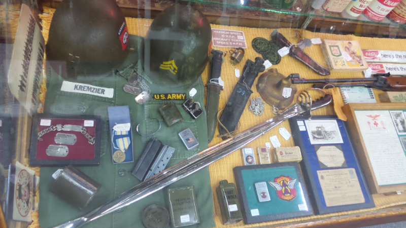A photo of a display case in dealer #0924's booth. There is a variety of vintage military gear on display, including medals and Army helmets. There is also heavy knives on display as well as patches.