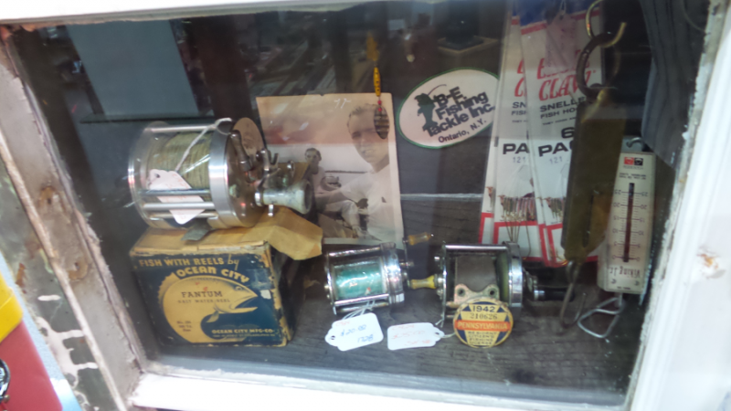 A photo of a display in Dealer #0924's booth. This display is themed around fishing, and has vintage fishing reels and hooks on sale.
