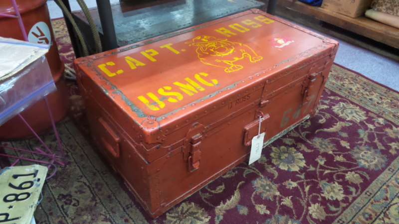 "A photo of a large chest for sale in Dealer #0924's booth. The chest is a light red and has ""CAPT. ROSS USMC"" stenciled in yellow, as well as a drawing of a bulldog with a military hat on its head."