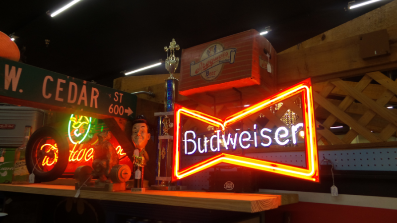 "A photo of Dealer #0924's booth. There are multiple signs on display, including a lit neon sign that reads ""Budweiser""."
