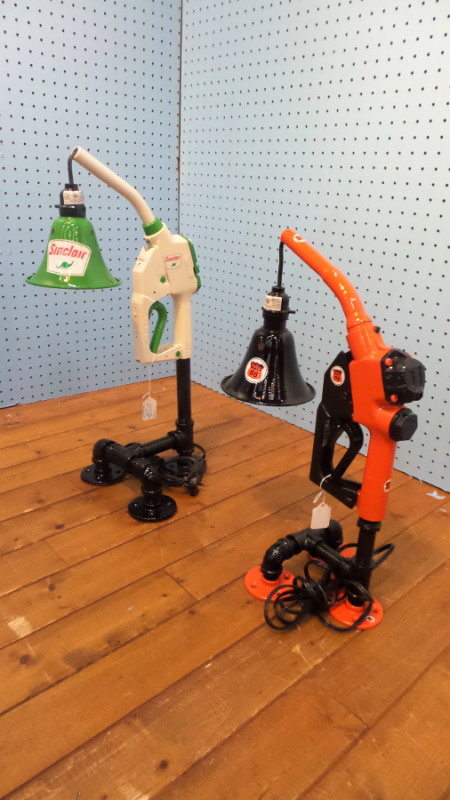 A pair of lamps made from gas pump handles and other industrial parts. One is green and white with the Sinclair logo and the other is orange and black with a Route 66 symbol printed on it.
