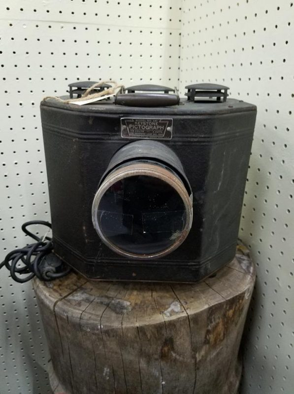 "A photo of a large, black box with a large lens on the front. It looks very old and reads ""KEYSTONE PICTOGRAPH"" on the top"