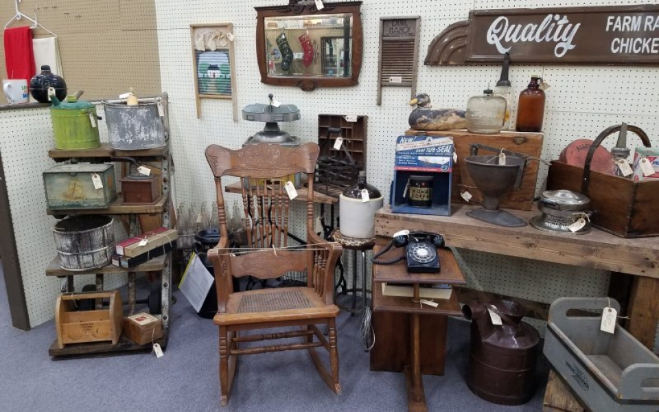 A photograph of a booth full of rustic and primitive items, including an antique rocking chair, a rotary telephone and crates and baskets