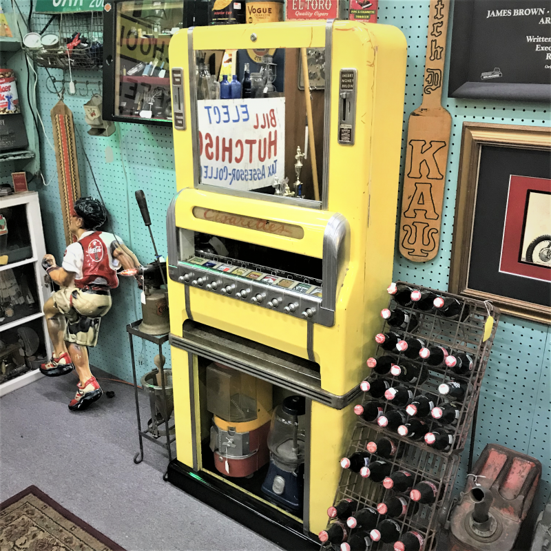 photo of retro yellow working cigarette machine, coca cola bottle racks, and candy dispensers